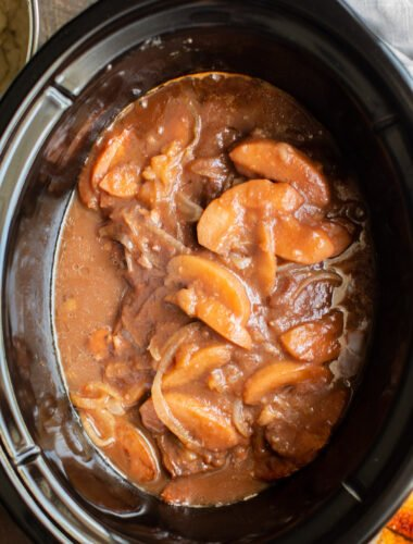 close up of apple butter pork chops in the slow cooker.