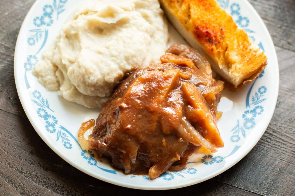 white plate with mashed potatoes, apple butter pork chops and garlic bread