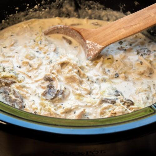 Artichoke mushroom chicken ready to serve with scoop in it