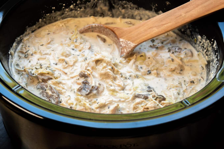 Artichoke mushroom chicken ready to serve with wooden spoon