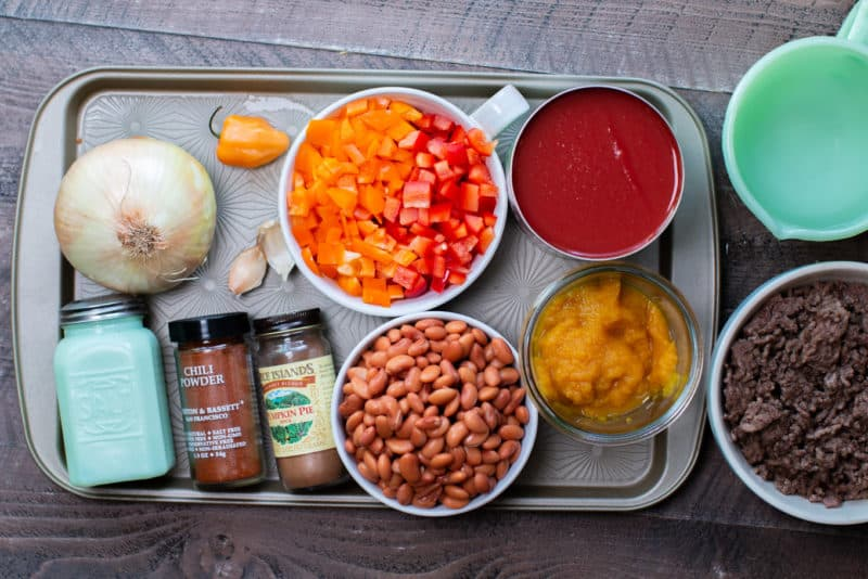 tomato sauce, bell peppers, pinto beans, seasonings, pumpkin puree, onion and habanero on a sheet pan.
