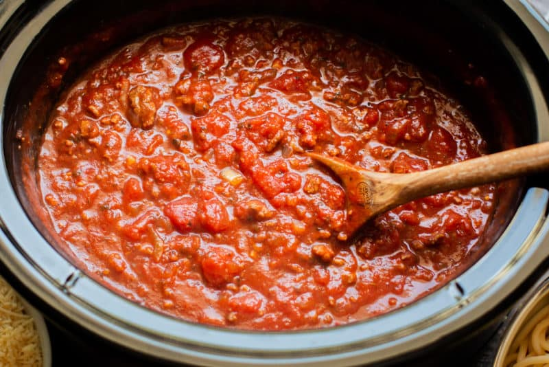 close up of cooked meaty spaghetti sauce in a slow cooker with a wooden spoon in it.