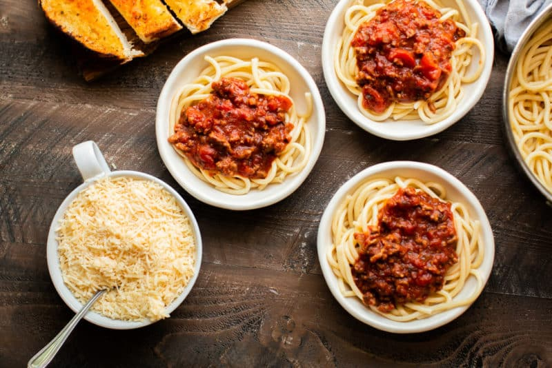 3 bowls of spaghetti with sauce on top.