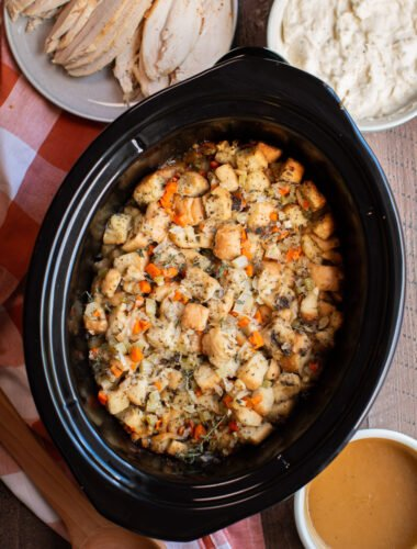 stuffing cooked in a slow cooker. Orange plaid napkin on the side.