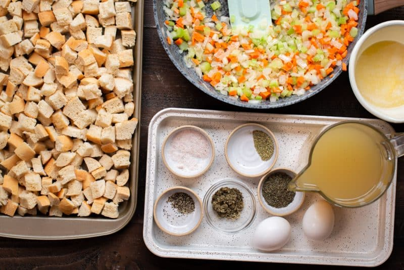 bread cubes on a sheet pan. Vegetables in skillet. Seasonings, chicken broth and eggs on small tray.