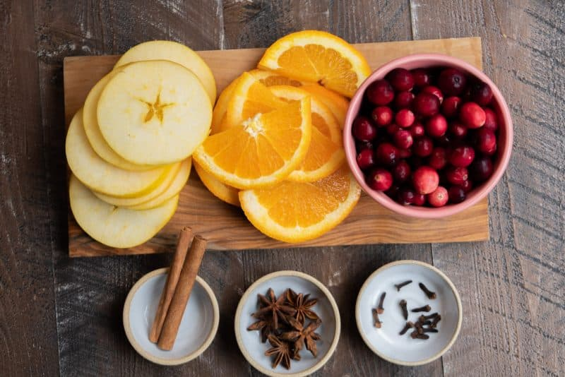 slice apples, sliced oranges, pink bowl of cranberries. Spices in small white dishes.