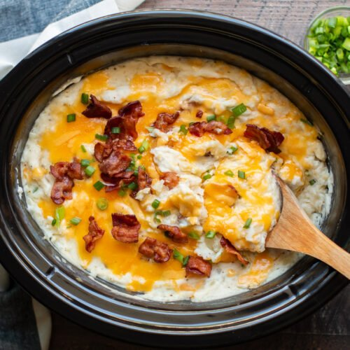 slow cooker full of baked potato casserole with wooden spoon in it.