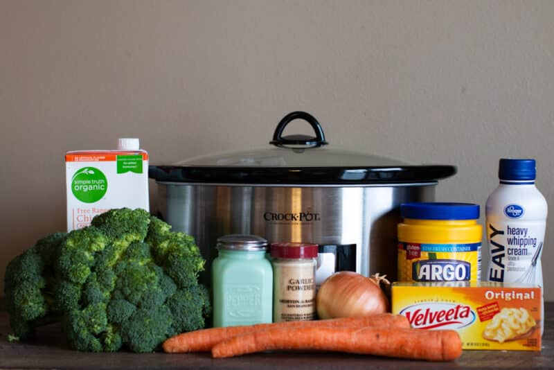Ingredients for broccoli cheese soup lined up in from of slow cooker