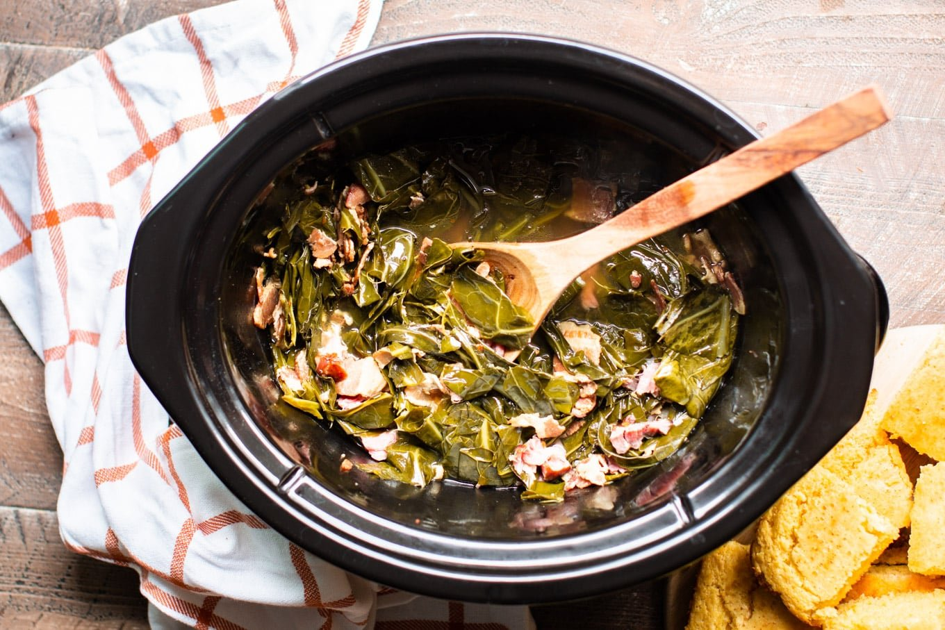 Finished collard green in slow cooker with spoon and cornbread
