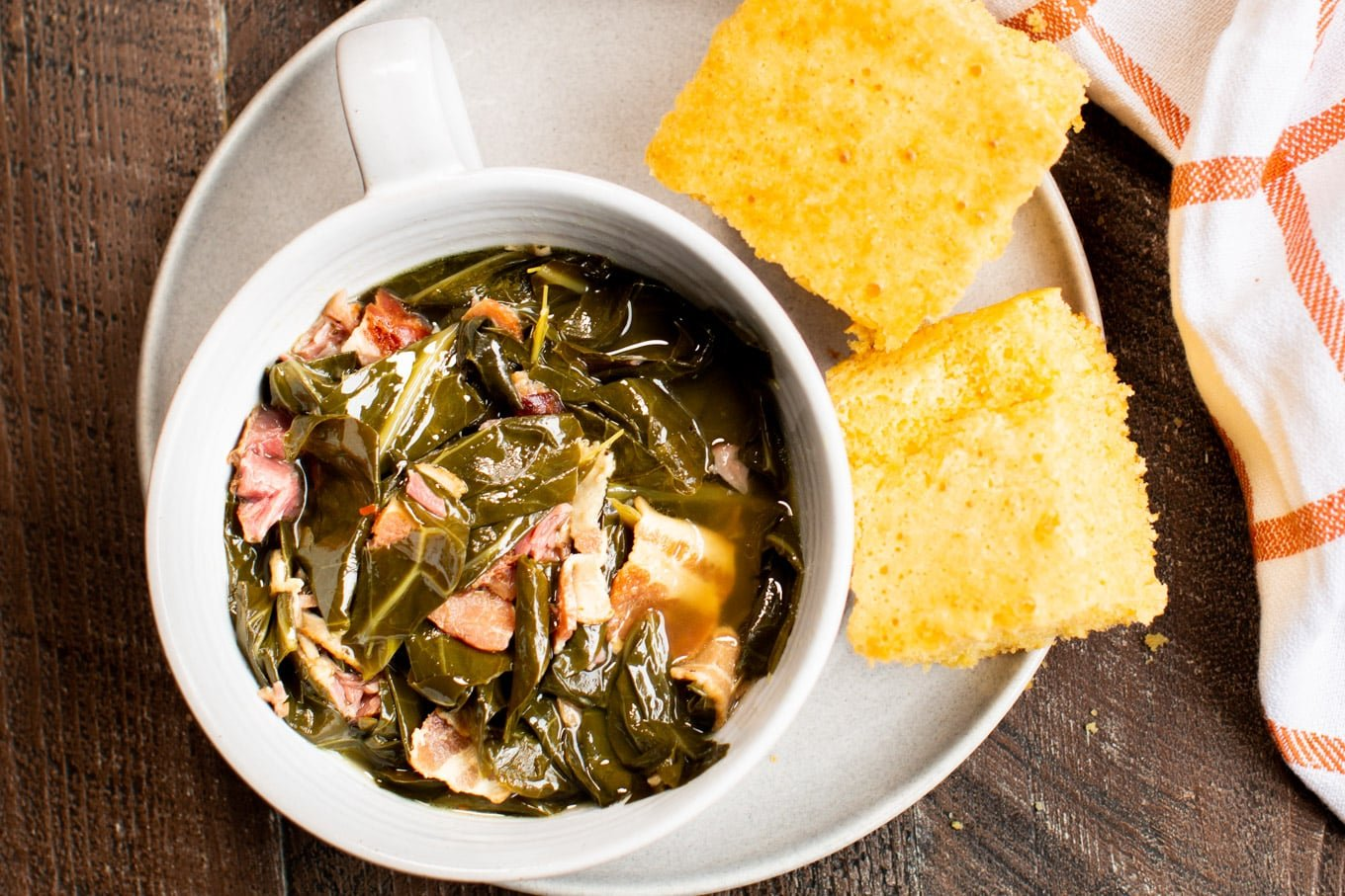 Collard green in bowl with cornbread on the side