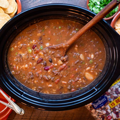 15 bean taco soup with spoon in it, chips and cheese on side