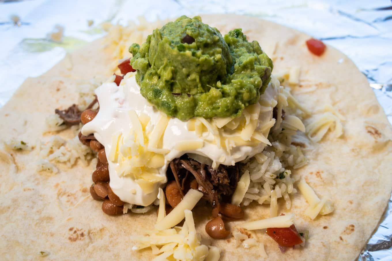 chipotle barbcoa burrito with guacamole and sour cream on top