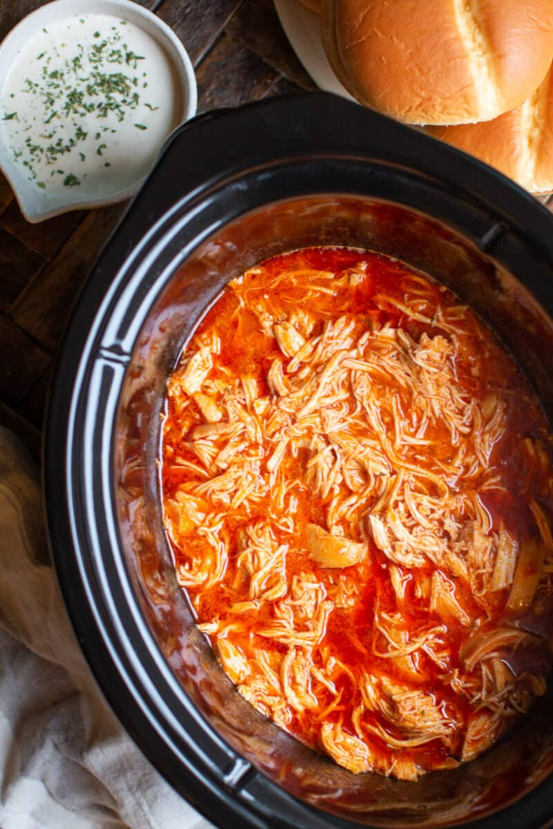 shredded buffalo chicken in slow cooker with ranch and buns on the side.