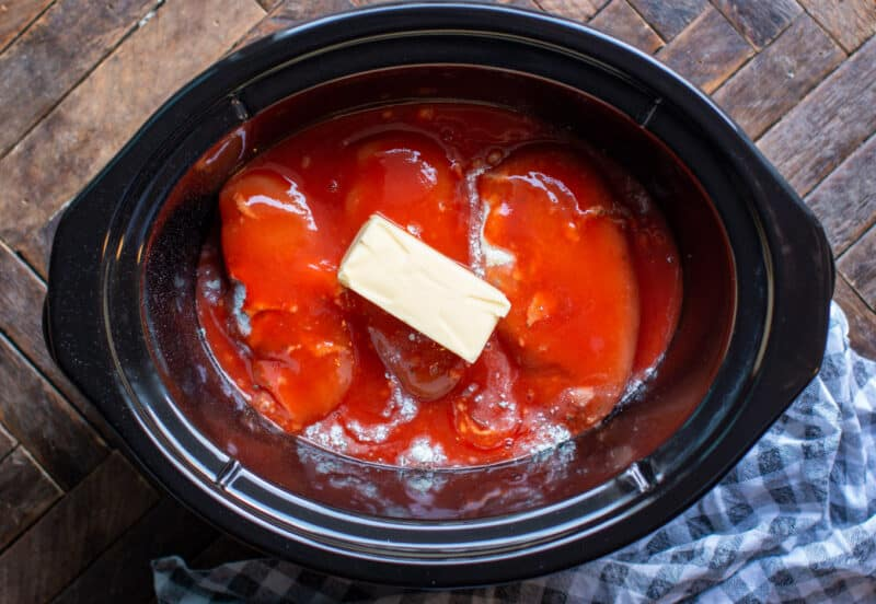 3 chicken breasts in slow cooker with ranch mix, buffalo sauce and a stick of butter on top.