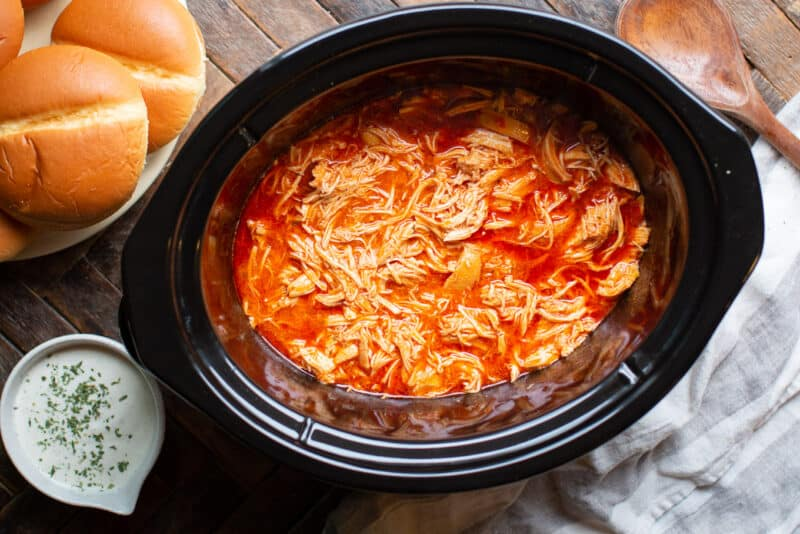 shredded chicken in slow cooker with buns, ranch, and wooden spoon on side.