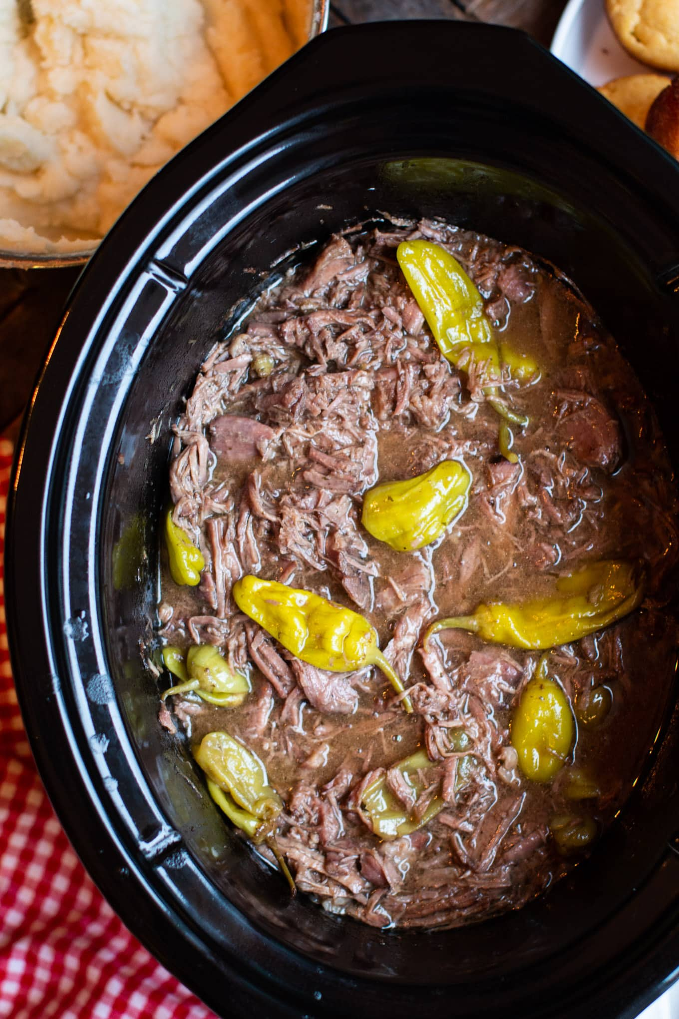 cooked pot roast with peppers in slow cooker.