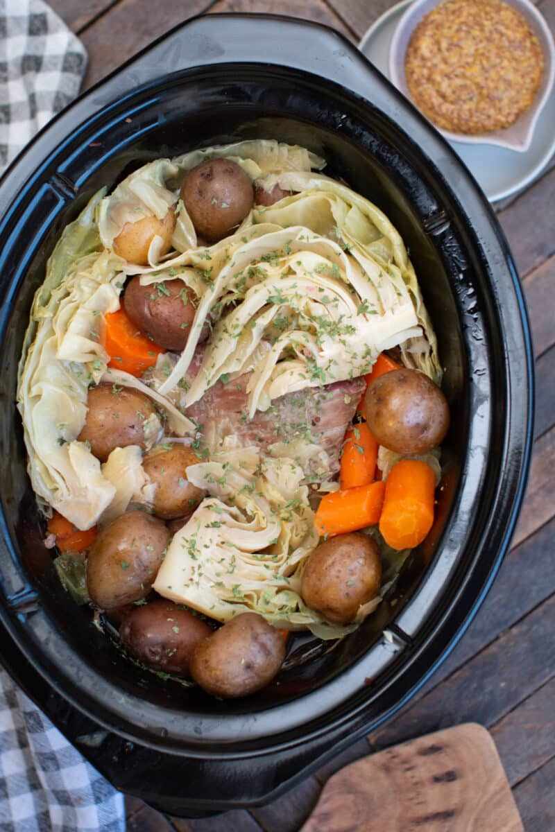cooked corned beef, potatoes, cabbage and carrots in slow cooker.