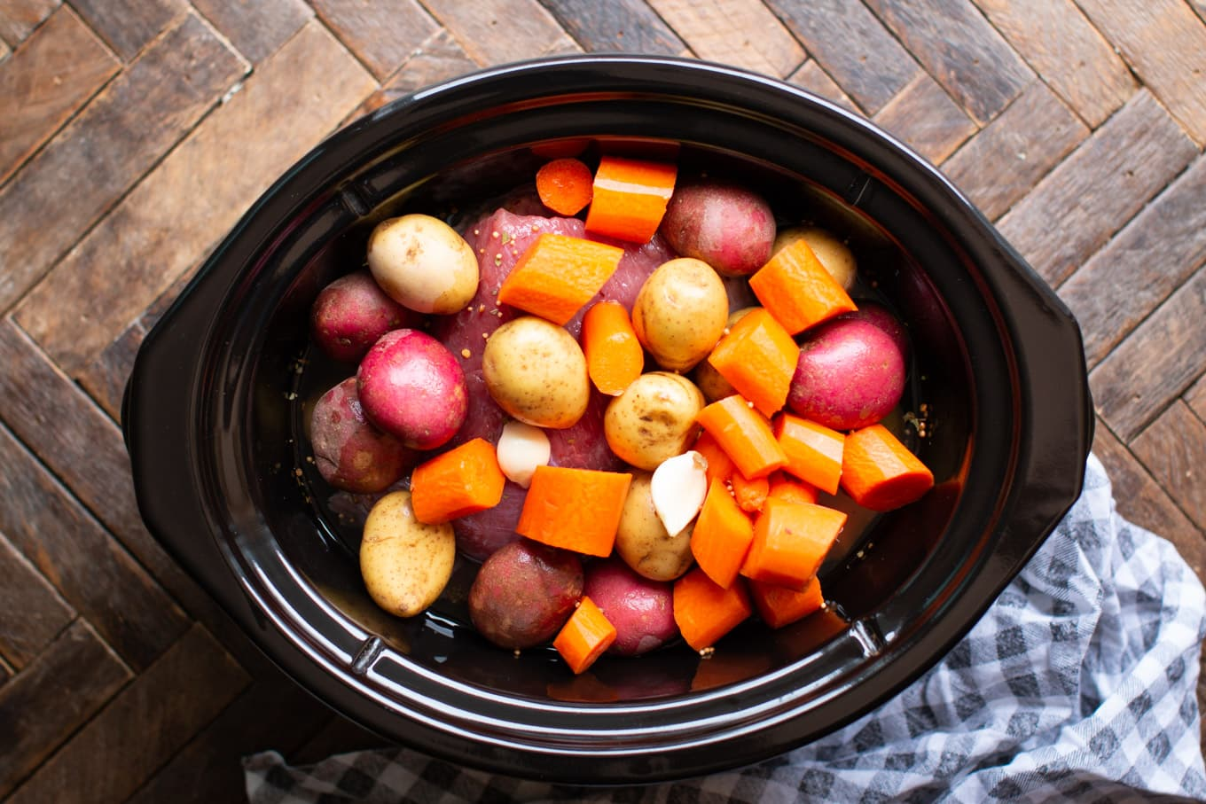 corned beef in crockpot with potatoes and carrots on top