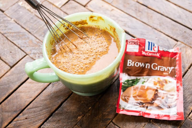 brown gravy mix packets next to bowl of prepared gravy