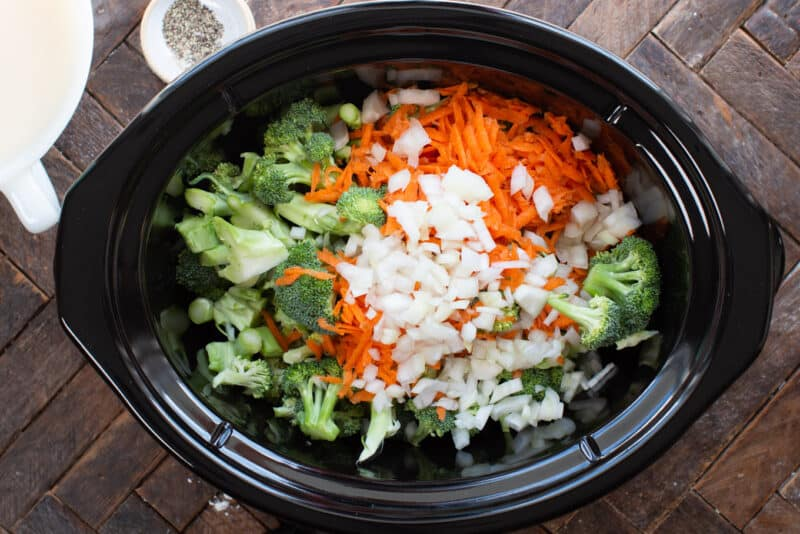 Slow cooker filled with broccoli, onions and shredded carrots