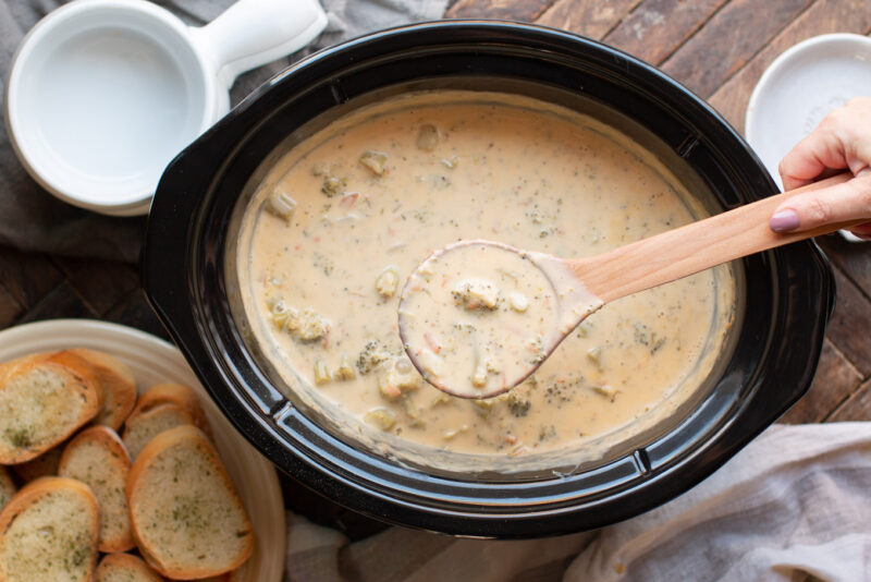broccoli cheese soup with large wooden spoon scooping soup out