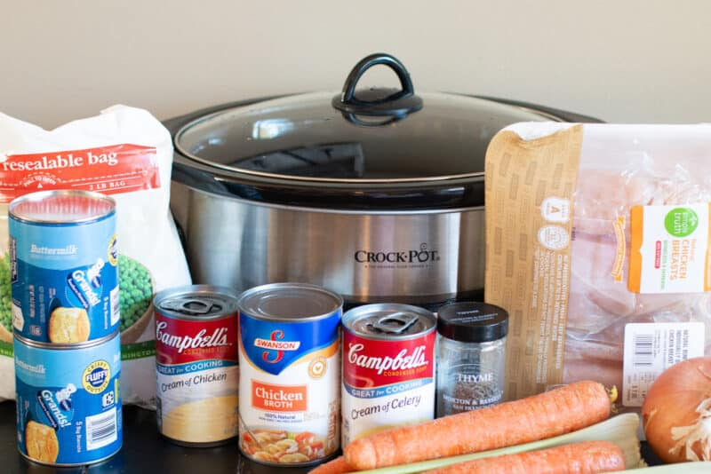 Ingredients for chicken and dumplings; chicken, cream soups, chicken broth, carrots, onion, celery, thyme and biscuits.