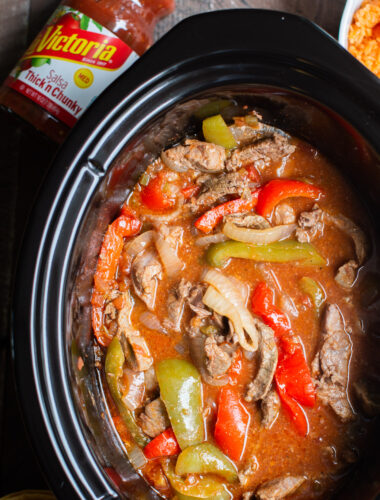 close up of beef strips, onion and bell peppers cooked in slow cooker.