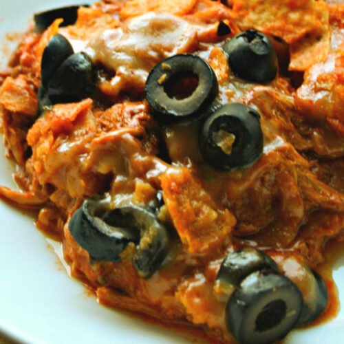 chicken dorito casserole in white bowl with olives on top