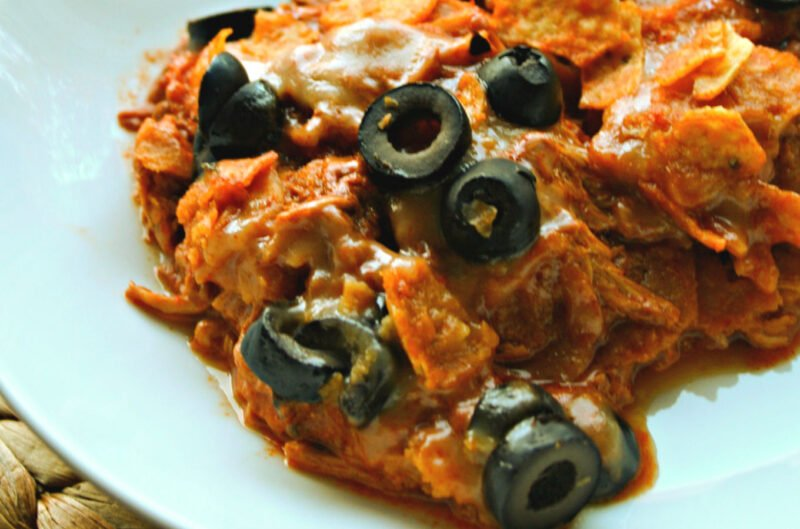 close up of chicken dorito casserole in bowl with olives on top
