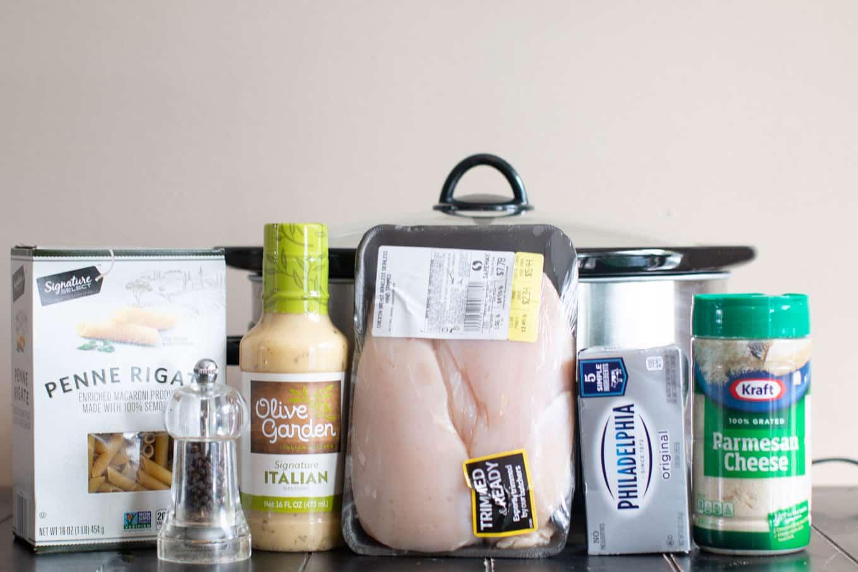 ingredients for olive garden chicken; italian dressing, chicken, pepper, cream cheese, and pasta.