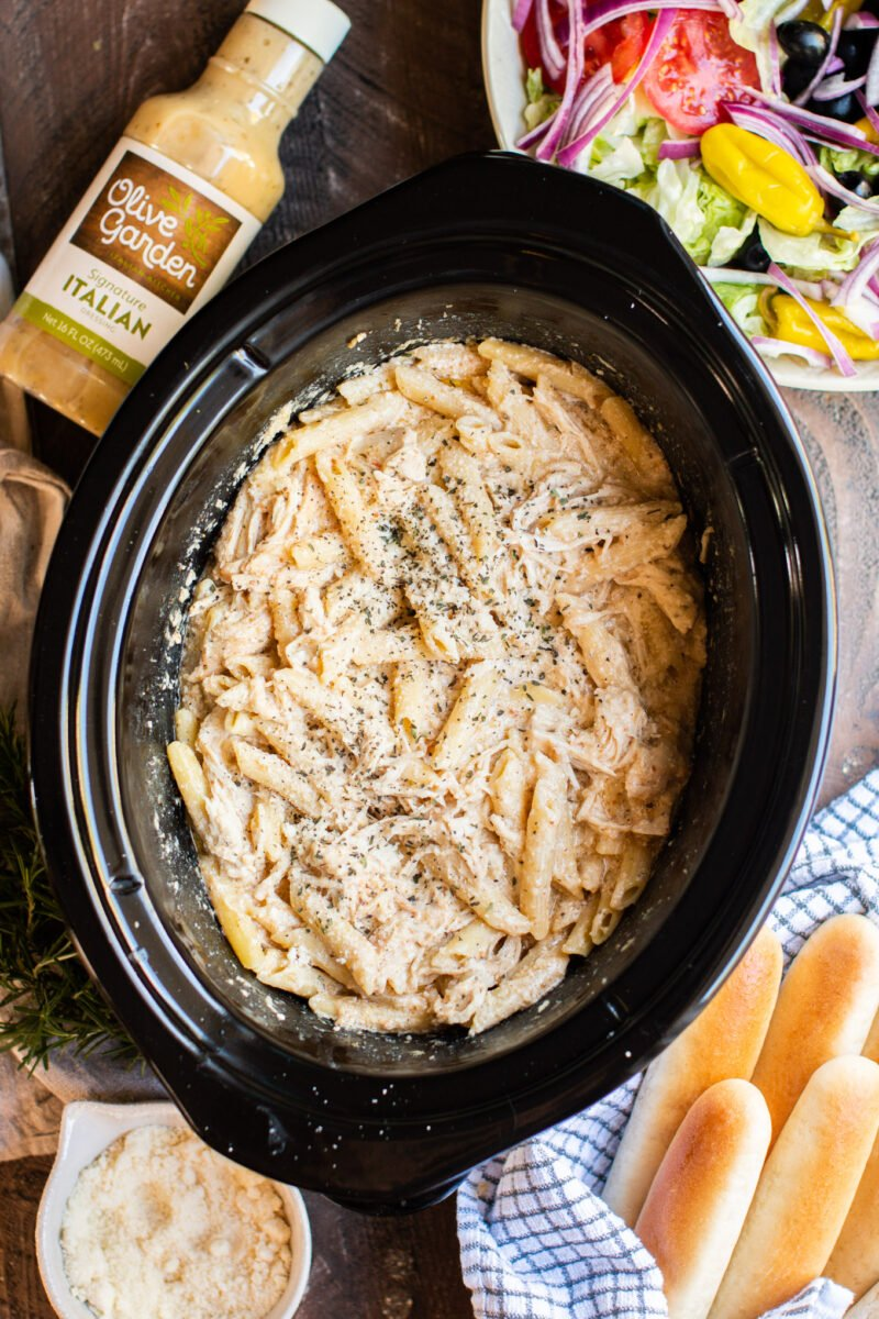 pasta in slow cooker with cheese on top. Breadsticks on the side.