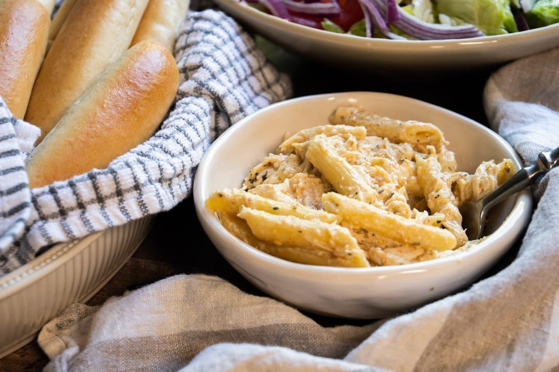 chicken penne pasta in white bowl