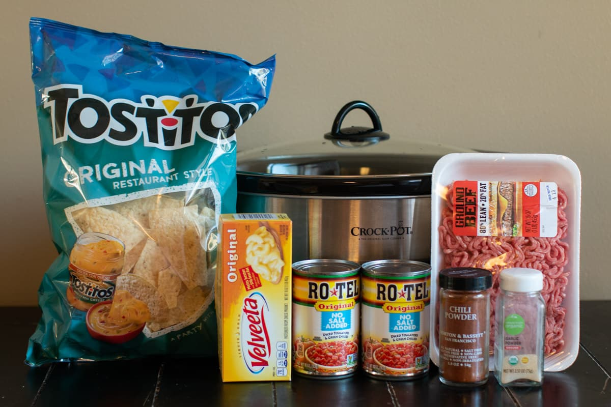 tostito chops, velveeta, 2 cans of rotel, package of ground beef and seasonings in front of slow cooker