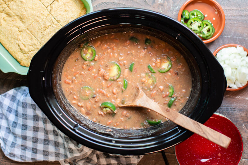 Cooked pinto beans in slow cooker with jalapenos and wooden spoon in them.