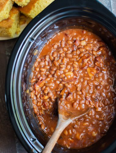 close up of baked beans in the slow cooker with spoon in it