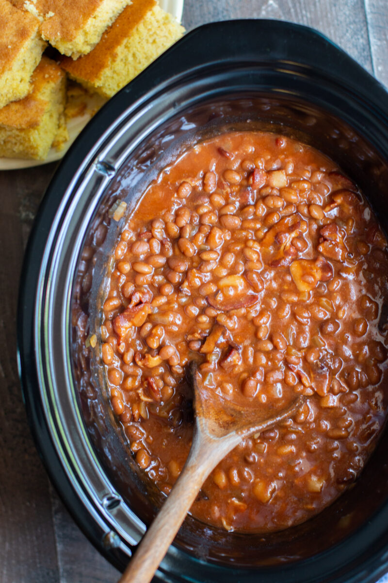 baked beans with bacon in black slow cooker with wooden spoon in them.
