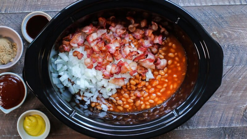 baked beans, halfway cooked bacon, onion in slow cooker unstirred.