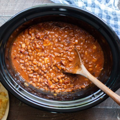 baked beans cooked in the slow cooker with wooden spoon in them.