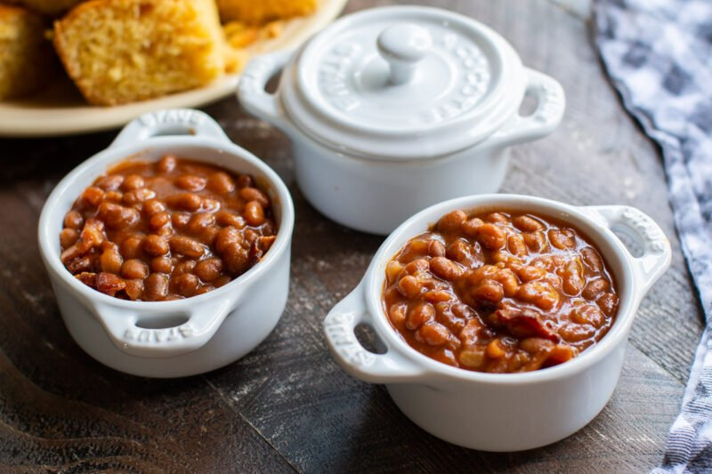 baked beans in small white bowls with cornbread in background.