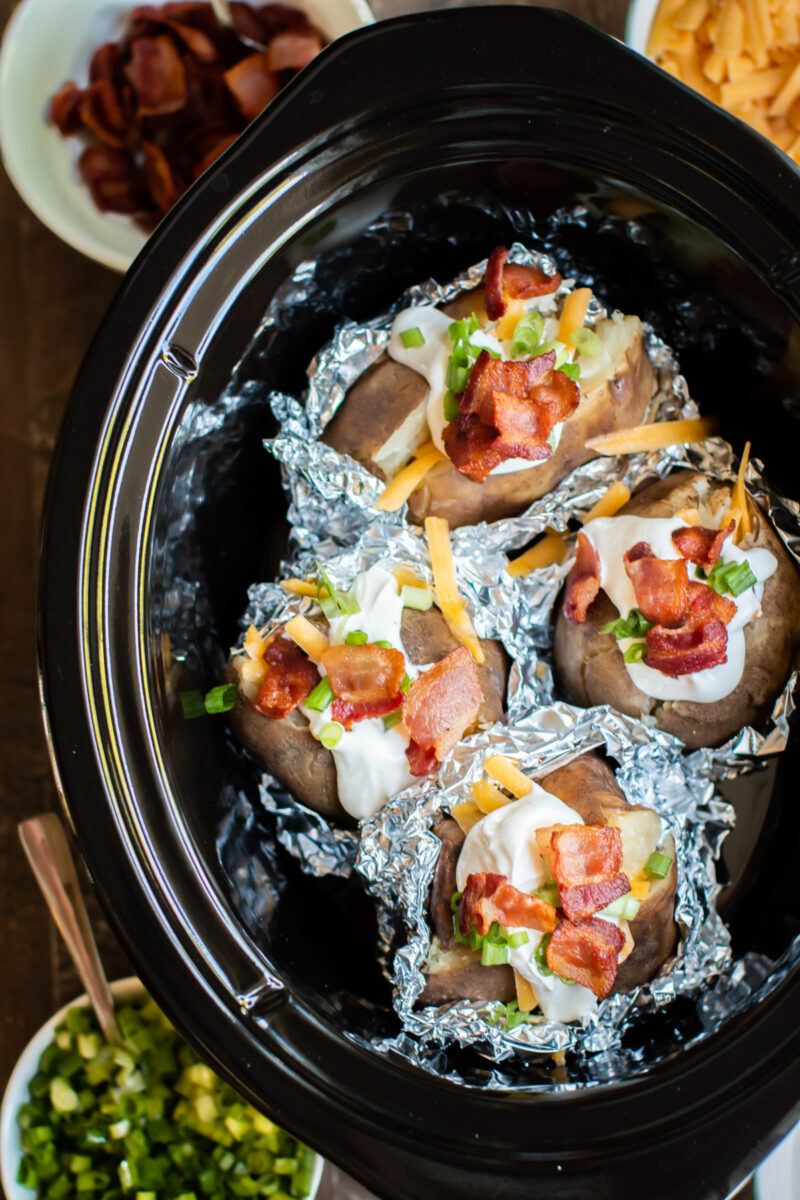 close up of baked potatoes in foil, halfway unwrapped with toppings