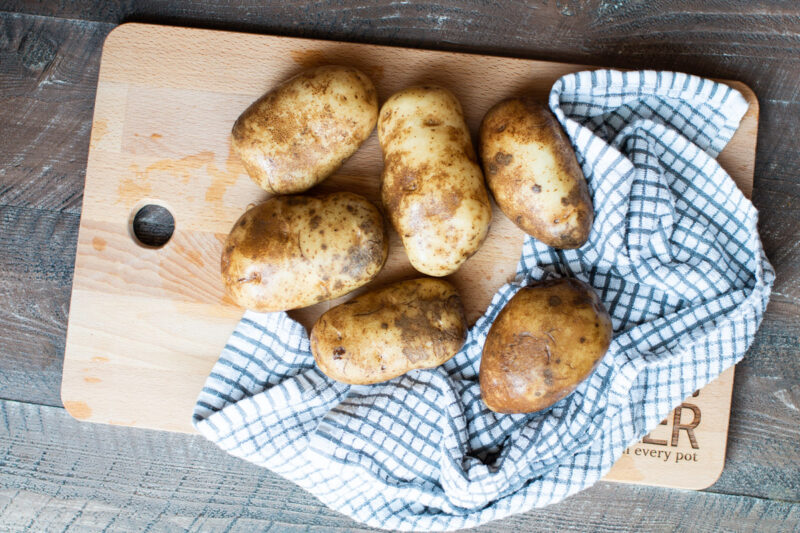 6 russet potatoes wet on cutting board