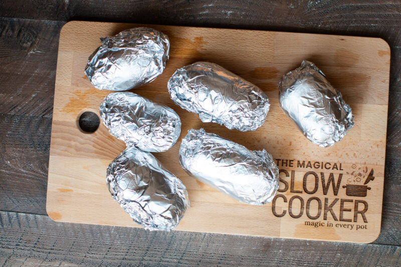 6 potatoes wrapped in foil on cutting board