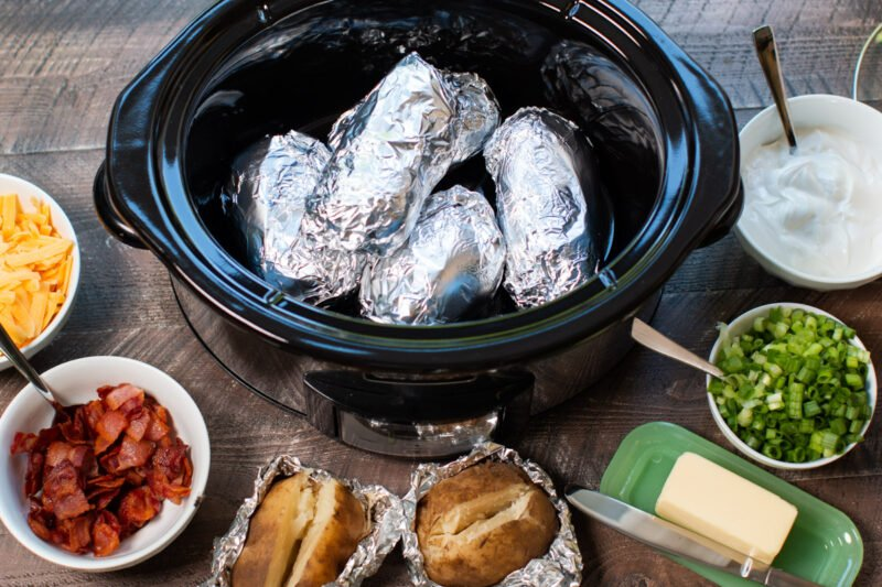 baked potato bar set up. Potatoes in slow cooker with toppings around the edge of slow cooker