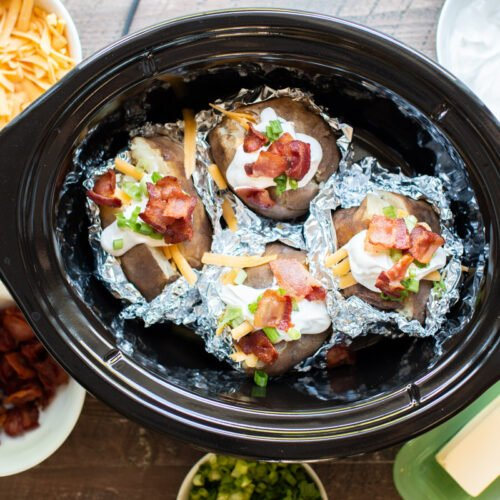 baked potatoes in slow cooker halfway wrapped in foil with toppings.