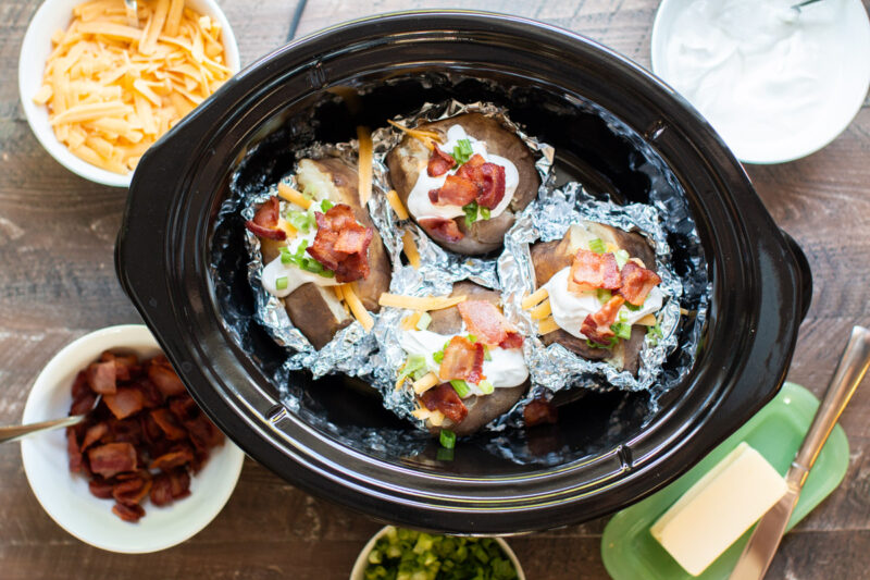 4 baked potatoes in slow cooker halfway unwrapped with toppings on each one