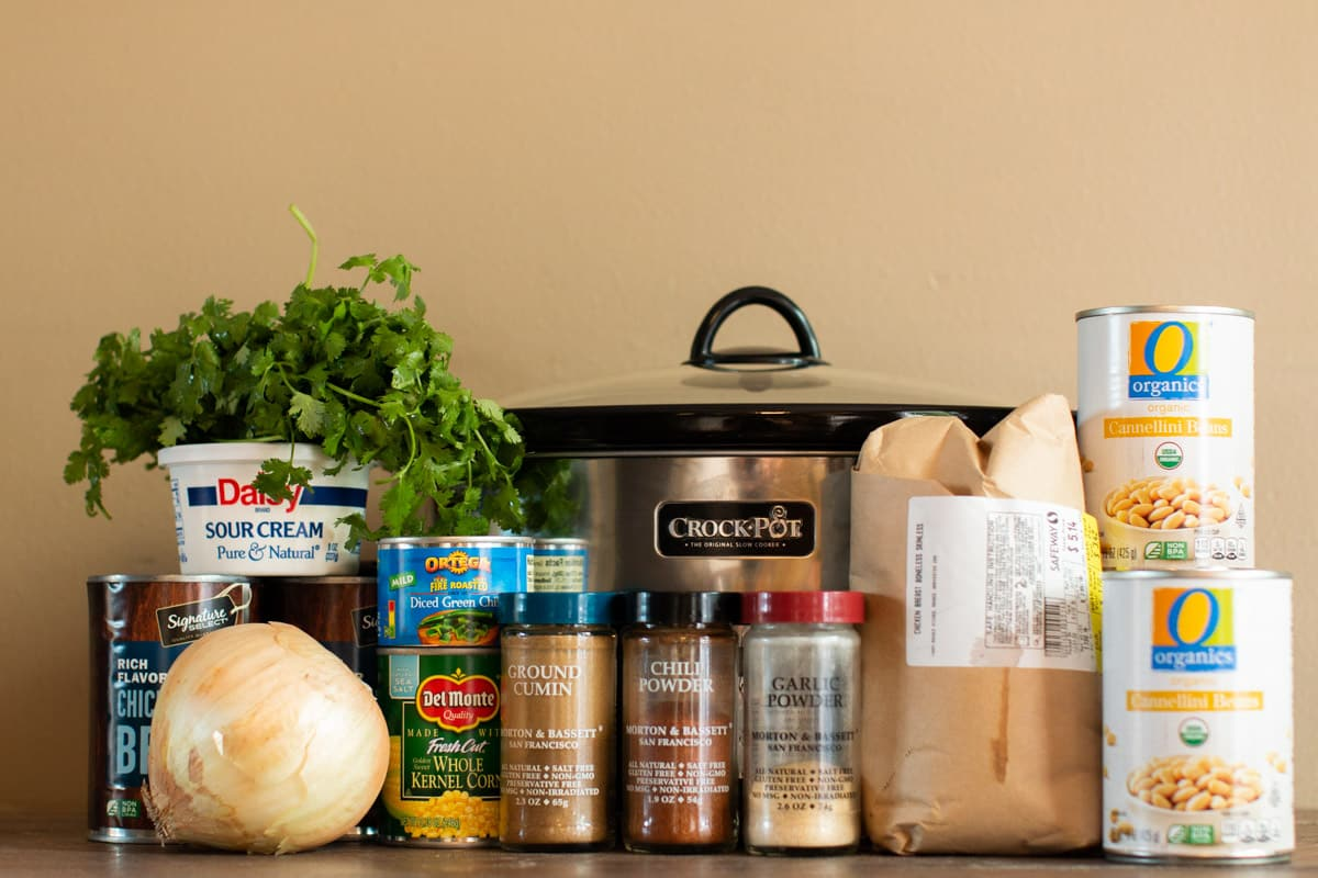 white beans, corn, sesonings, onion, chicken broth, sour cream, cilantro and chicken in front of slow cooker.