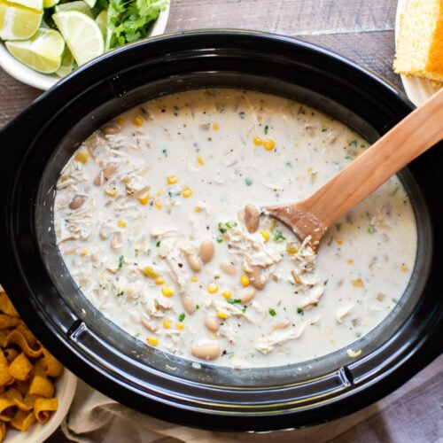 white chicken chili in slow cooker with wooden spoon in it.