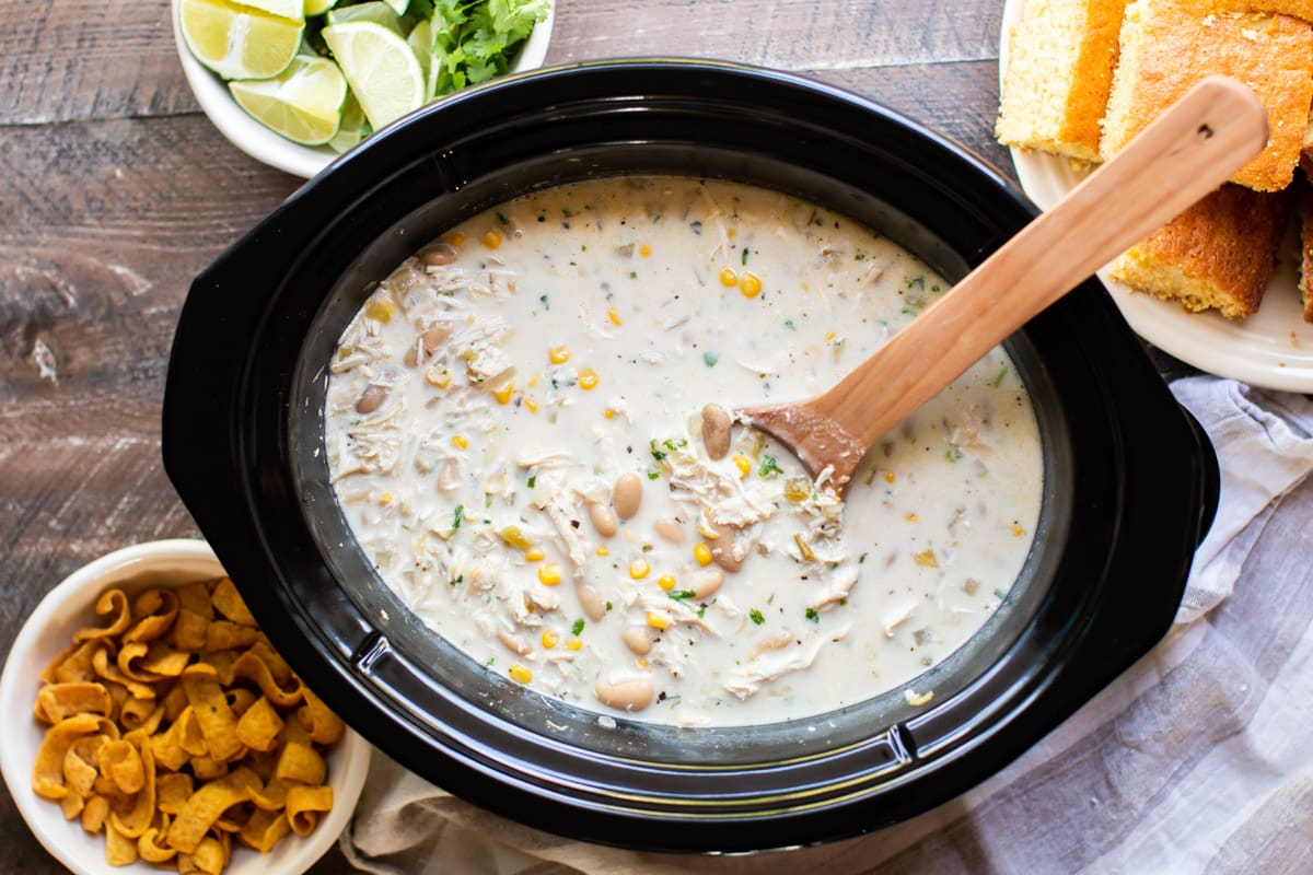 white chili with chicken and corn with fritos and cornbread on the side