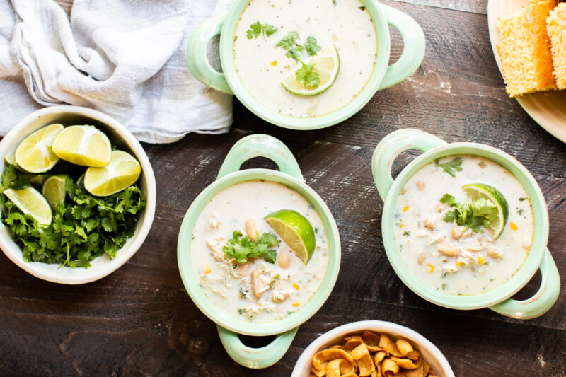 3 bowls of white chili with bowl of cilantro and limes on side