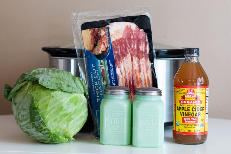 large head cabbage, bacon, salt, pepper, and bacon in front of a slow cooker.